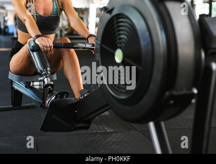 Cropped photo of sporty handicapped woman in tracksuit working out and doing crossfit exercises on training simulator in gym - Stock Photo