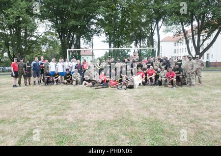 U.S. Soldiers assigned to the 91st Engineer Battalion, 1st Armored Combat Brigade Team, 1st Calvary Division and to Company B, 151st Expeditionary Signal Battalion, South Carolina National Guard, pose for a group photo with Soldiers assigned to the 23rd Artillery Brigade, Polish Land Forces during the 243rd Army Birthday celebration held at the Polish Land Forces base in Boleslawiec, Poland, June 14, 2018. The joint celebration included a base-wide run, field events, and a cake cutting ceremony. - Stock Photo