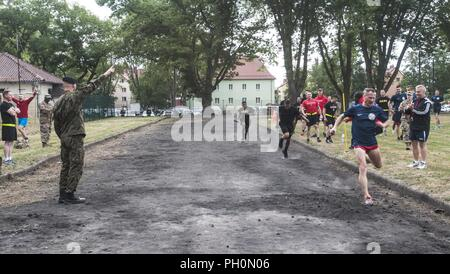 A 23rd Artillery Brigade, Polish Land Forces soldier crosses the finish line first during the 4x400 relay race held in celebration of the 243rd Army Birthday celebration held at the Polish Land Forces base in Boleslawiec, Poland, June 14, 2018. U.S. Soldiers assigned to the 91st Engineer Battalion, 1st Armored Combat Brigade Team, 1st Calvary Division, and Company B, 151st Expeditionary Signal Battalion, South Carolina National Guard, placed second and third. - Stock Photo