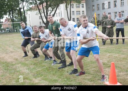 Soldiers assigned to the 23rd Artillery Brigade, Polish Land Forces prepare for a tug of war match against the U.S. Soldiers assigned to the 91st Engineer Battalion, 1st Armored Combat Brigade Team, 1st Calvary Division during the 243rd Army Birthday celebration held at the Polish Land Forces base in Boleslawiec, Poland, June 14, 2018. The joint celebration included a base-wide run, field events, and a cake cutting ceremony. - Stock Photo