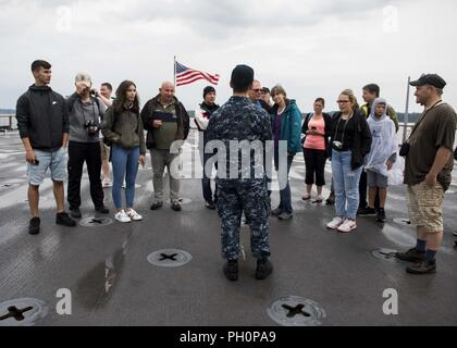 SEA (June 16, 2018) Hospital Corpsman 2nd Class Andy Kim, center, gives a tour of the Harpers Ferry-class dock landing ship USS Oak Hill (LSD 51) in Kiel, Germany, during Kiel Week 2018, June 16. Oak Hill, home-ported in Virginia Beach, Virginia, is conducting naval operations in the U.S. 6th Fleet area of operations. - Stock Photo