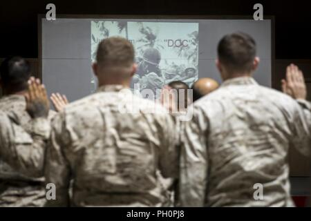 UNDISCLOSED LOCATION, MIDDLE EAST – U.S. Navy Corpsman raise their right hands and recite the Corpsman Pledge at the conclusion of the 120th Hospital Corpsman Birthday Ceremony, held by Special Purpose Marine Air-Ground Task Force, Crisis Response-Central Command June 17, 2018. U.S. Navy Corpsmen are a vital part of the Marine Corps team and serve alongside their Marine brothers and sisters in every clime and place. - Stock Photo