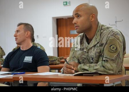 2nd Lt. Matthew Kemelek, assistant operations officer, Headquarters and Headquarters Troop, 1st Squadron, 2d Cavalry Regiment, listens attentively to Kasia Kardasiewicz, a Polish linguist for Mission Essential currently working at the Battle Group Poland, as she teaches grammar rules during a Polish language class at the Bemowo Piskie Training Area, Poland, June 19, 2018. Battle Group Poland is a unique, multinational coalition of U.S., U.K., Croatian and Romanian Soldiers who serve with the Polish 15th Mechanized Brigade as a deterrence force in support of NATO's enhanced Forward Presence ini - Stock Photo