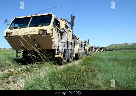 Soldiers from the 137th Transportation Company, Kansas Army National Guard, convoy to Red Shirt, S.D., June 15, 2018. These military vehicles allow large amounts of timber to be delivered to Native American reservations in support of the timber haul operation and Golden Coyote training exercise. - Stock Photo