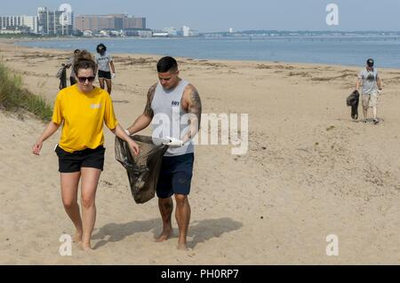 VIRGINIA BEACH, Va. (June 18, 2018) Sailors assigned to the aircraft carrier USS George H.W. Bush (CVN 77) clean up the beach at First Landing State Park. As a birthday tribute to the ship's namesake, and representing his famous 'Thousand Points of Light' speech, approximately 1,000 GHWB crew members took part in one of the largest single-day community relation (COMREL) events at 44 different locations throughout the Hampton Roads area. George H.W. Bush turned 94 on June 12. - Stock Photo