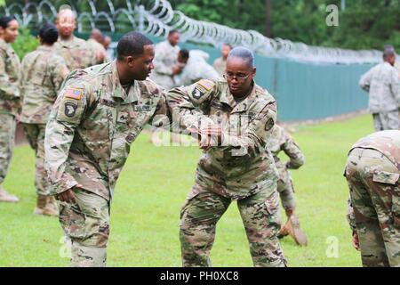 Staff Sgt. Kellen Phillips and Sgt. Brenda Sales-Belardo, Virgin Islands National Guard 661st Military Police Law and Order Detachment, practice holding techniques during a Mechanical Control Holds (MACH) course as part of their annual training at Ft. Polk, LA, June 21, 2018. This training reiterated and put to use the members of the 661st Military Police Law and Order Detachment military occupational specialty. - Stock Photo