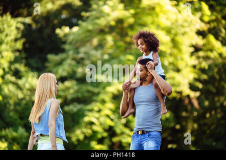 Portrait of young father carrying his daughter on his back - Stock Photo