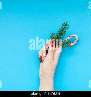 New Year Christmas top view Xmas holiday celebration woman hand red manicure holding fir branch sweet cane copy space turquoise blue color paper backg - Stock Photo