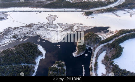 Aerial view at northern rail road passing along partially frozen lake in forest on cold winter day, north of Karelia, Russia - Stock Photo