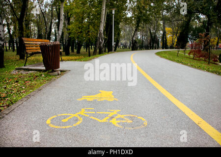 Signs cycling and inline skating track on the asphalt. Part of the background track for roller skating and cycling with a painted sign. Park in autumn - Stock Photo