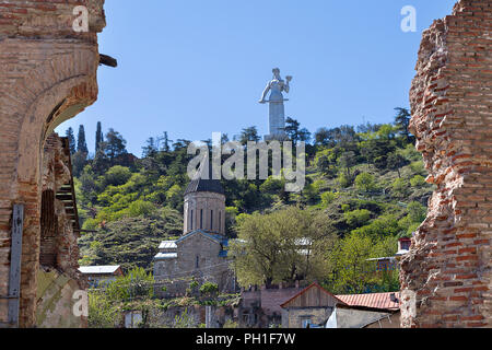 Statue of Mother of Georgia, through old brick walls, in Tbilisi, Georgia. - Stock Photo