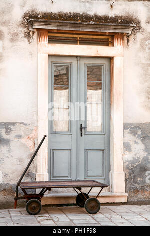 Old vintage entrance doors with rusty trolley in front of entrance. - Stock Photo
