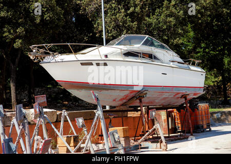 Yacht motor boat in the harbor. White yacht motorboat on the maintenance structure at the harbor. Wooden yacht out of the sea for maintenance port. - Stock Photo