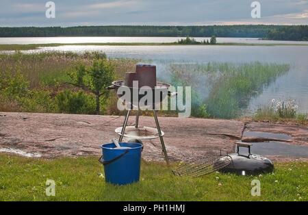 Small barbecue setup on the rock with beautiful sunset view over a lake, Sweden - Stock Photo