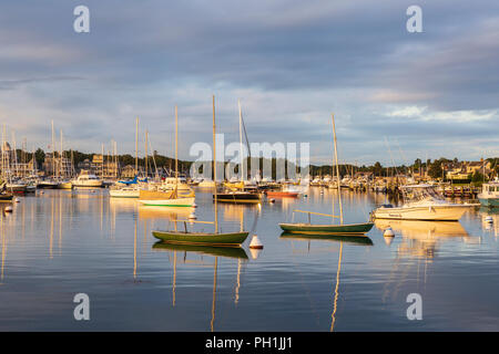The rising sun adds color to dramatic clouds over sunlit boats in the harbor shortly after sunrise in Oak Bluffs, Massachusetts on Martha's Vineyard. - Stock Photo