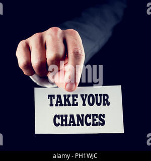 Businessman in a suit holding out a small white card with the motivational message and words - Take Your Chances - close up of his hand on a dark back - Stock Photo
