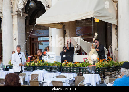 People listening to classical music at Gran Caffe Chioggia, Piazza San Marco, Venice, Veneto, italy while enjoying drinks. Live performance of Italian - Stock Photo