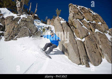 Snowboarder in blue jacket riding through rocks on a bluebird powder day at Mt. Rose Ski Tahoe near Reno, Nevada, North America. - Stock Photo