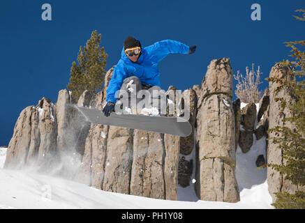 Snowboarder in blue jacket jumping through rocks on a bluebird powder day at Mt. Rose Ski Tahoe near Reno, Nevada, North America. - Stock Photo