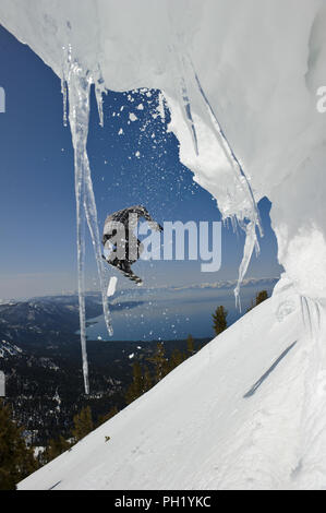 Snowboarder Nick Langkamp on top of Incline Peak with North Lake Tahoe in the background on a clear day. - Stock Photo