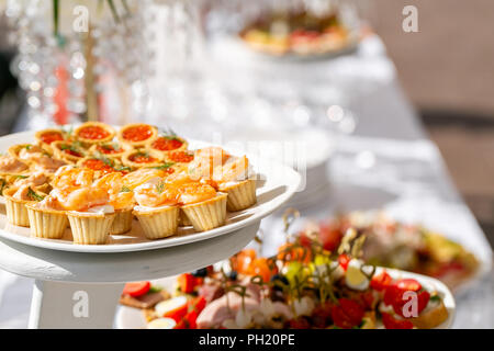 solemn banquet. Lot of glasses champagne or wine on the table in restaurant. buffet table with lots of delicious snacks. canapes, bruschetta, and little desserts on wooden plate board - Stock Photo