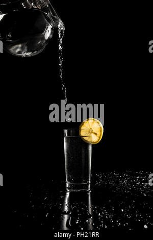 Pouring water in to a tall glass garnished with a slice of fresh lemon from a glass jug held at a height with spillage around the glass on a dark back - Stock Photo