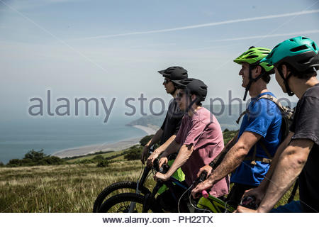 Four men on mountain bikes in Porlock Weir, England - Stock Photo