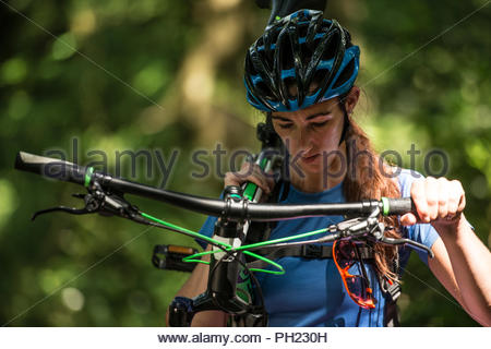 Woman carrying mountain bike in forest - Stock Photo