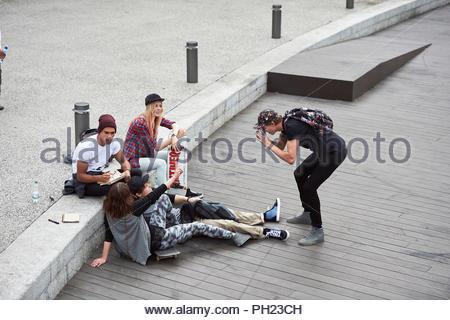 Teenage boy photographing friends on boardwalk - Stock Photo