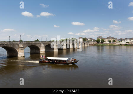 Town of Saumur, France. Picturesque view of the boat transiting under Saumur's Cessart Bridge on the River Loire. - Stock Photo