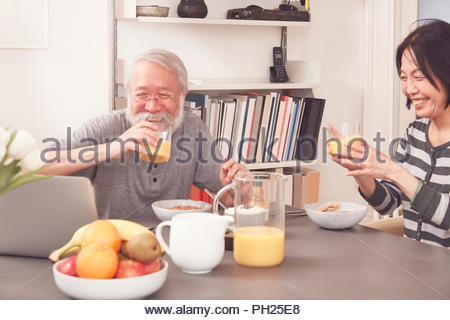 Senior couple using laptop at breakfast table - Stock Photo
