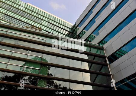 Abstract glass exterior of modern office building in downtown Singapore with symmetrical patterns, reflections and perspective as abstract background - Stock Photo
