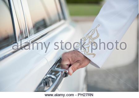Hand of chauffer on door handle - Stock Photo