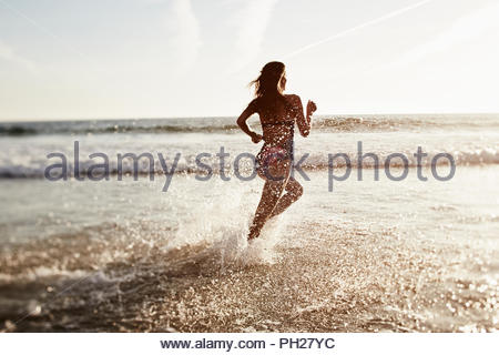 Young woman running in sea - Stock Photo