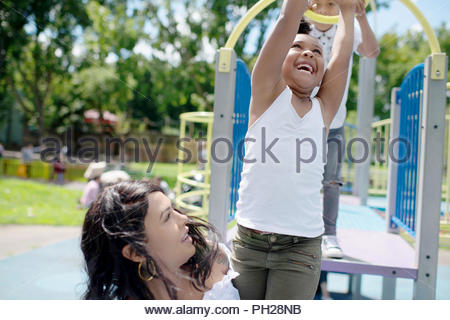 Mother and daughter playing on playground - Stock Photo