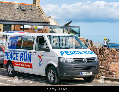 West Bay, North Berwick, East Lothian, Scotland, UK, 30th August 2018. Sir Chinmoy Oneness-Home Peace run runners VW minibus in the sunshine in North Berwick. The runners will run along the coastline to Dirleton carrying a flaming peace torch and flags. The 2018 European run started in February in Sofia, Bulgaria and will finish in Portugal. The runners and torch will be carried by a team of international runners through Northern Ireland, Ireland, Wales and England over 16 days starting from today. he Peace Run is a global torch relay promoting world peace - Stock Photo