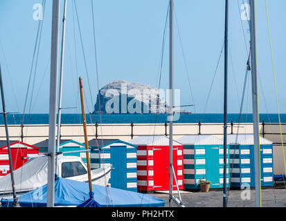 North Berwick, East Lothian, Scotland, UK, 30th August 2018. UK weather: A warm and sunny day at the end of the Summer in the seaside town of North Berwick. A view across North Berwick harbour with colourful striped bathing huts and boats looking towards the Bass Rock, the largest gannet colony. Gannets mass around the Bass Rock. The gannets will be ready to leave in a month's time - Stock Photo