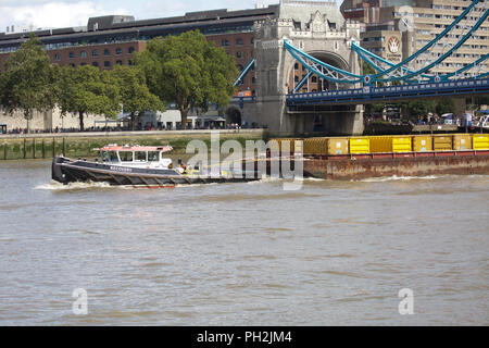 London,UK,30th August 2018,A tug boat pulls containers on the River Thames in London. The weather forecast is to remain cloudy,sunny and settled for at least the next week into early September. Credit Keith Larby/Alamy Live News - Stock Photo