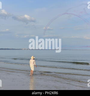 Bournemouth, Dorset, UK, 30th August 2018. The Red Arrows aerobatic display team perform against blue skies on the first day of the air show. A woman stands in the sea and watches from Shell Bay, Studland. Credit: Paul Biggins/Alamy Live News - Stock Photo
