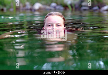 Girl half submerged swimming in a natural pool. - Stock Photo