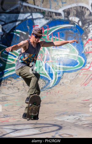 Young Man Skateboarding at the Riverside River Yard Skateboard Bowl, Great Fall, Montana, USA - Stock Photo
