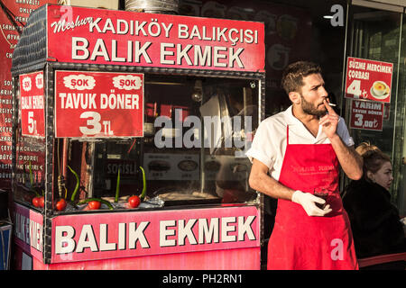 ISTANBUL, TURKEY - DECEMBER 27, 2015: Balik Ekmek seller on the Asian side of Istanbul. Balik Ekmek is the traditional grilled Fish Sandiwch sold all  - Stock Photo