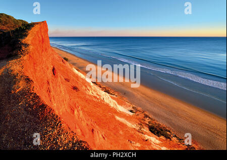 Scenic evening atmosphere at long sand beach with red sand cliffs and calm ocean - Stock Photo