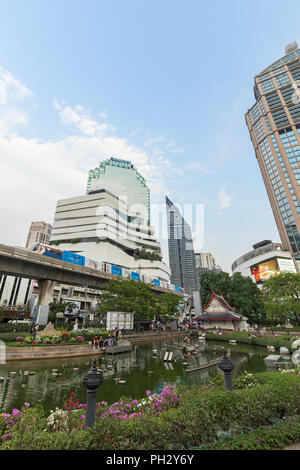 View of a pond at the Benchasiri Park, modern buildings and a skytrain in downtown Bangkok, Thailand. - Stock Photo