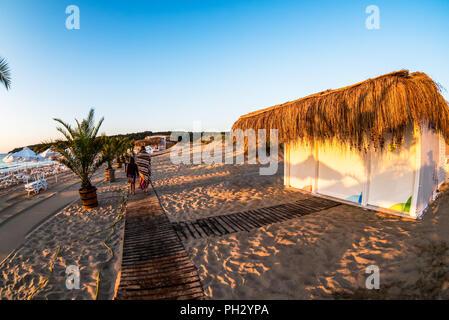 Sun at the horizon lights wooden boardwalk over the sand dunes to wild beach - Stock Photo