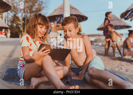 Portrait of positive children playing with digital tablet together on sandy beach. - Stock Photo
