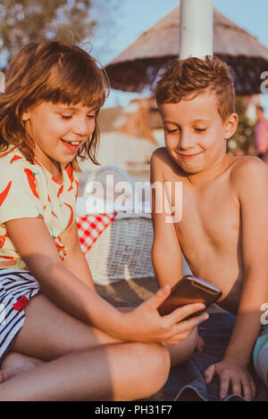 Portrait of positive happy children playing with mobile phones on sandy beach together - Stock Photo