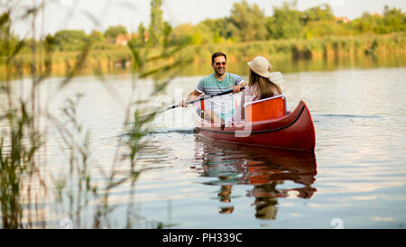 Loving couple rowing on the lake at summer day - Stock Photo