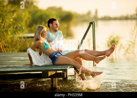 Romantic couple sitting on the wooden pier on the lake at sunny day - Stock Photo
