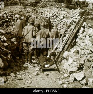 German wounded, c1914-c1918. An injured German soldier lies on a stretcher. French soldiers are taking prisoners of war. Photograph from a series of glass plate stereoview images depicting scenes from World War I (1914-1918). - Stock Photo